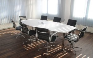 A conference table in a well-lit room surrounded by empty office chairs.