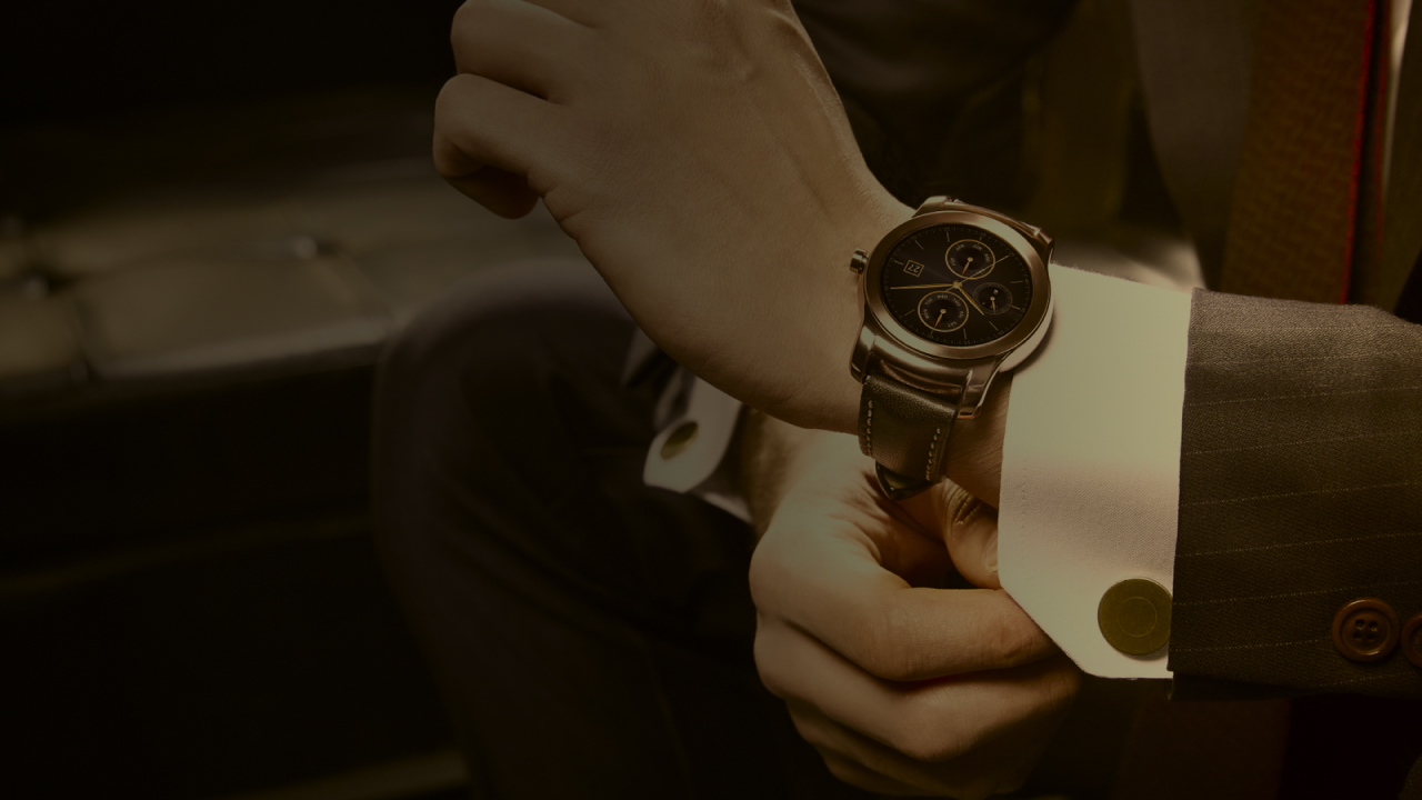 Well-dressed man adjusts expensive watch.